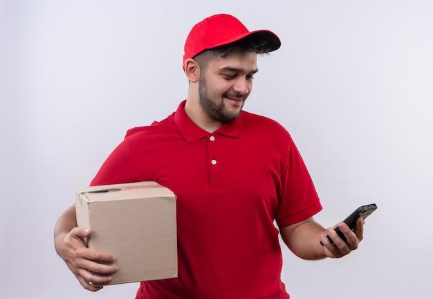 Młody człowiek dostawy w czerwonym mundurze i wpr, trzymając pakiet pole, patrząc na ekran swojego smartfona z uśmiechem