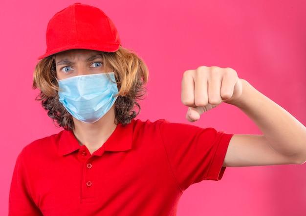Młody człowiek dostawy w czerwonym mundurze na sobie maskę medyczną pokazując pięść do kamery agresywny wyraz twarzy na tle odizolowanej pięści