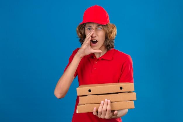 Młody człowiek dostawy w czerwonym mundurze, trzymając pudełka po pizzy, trzymając rękę w pobliżu otwartych ust, krzycząc na na białym tle niebieskim tle