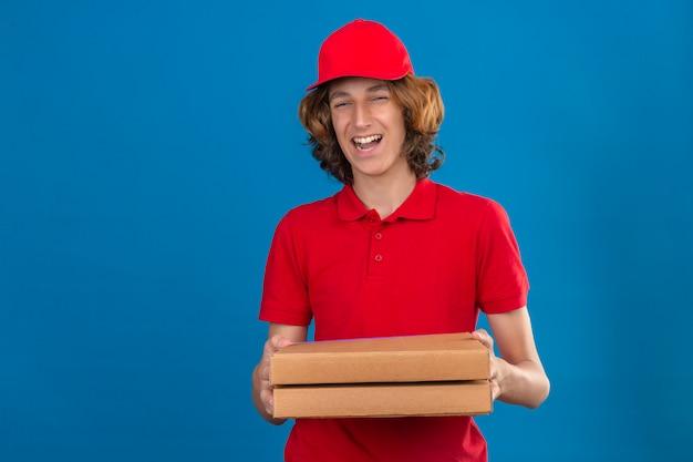 Młody człowiek dostawy w czerwonym mundurze, trzymając pudełka po pizzy, uśmiechając się radośnie z radosną miną na odosobnionym niebieskim tle