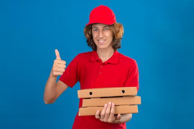 Młody człowiek dostawy w czerwonym mundurze, trzymając pudełka po pizzy, uśmiechając się z radosną miną pokazując kciuk do góry na odosobnionym niebieskim tle