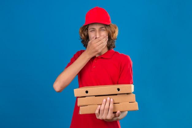 Młody człowiek dostawy w czerwonym mundurze, trzymając pudełka po pizzy ziewanie obejmujące usta ręką na na białym tle niebieskim tle