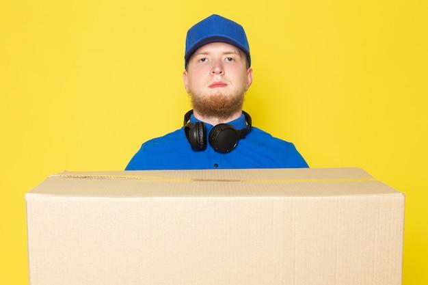 Młody człowiek dostawy w niebieskim niebieskim polo niebieskiej czapce biały dżins plecak trzyma pudełko na żółtym