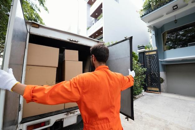 Młody człowiek dostawy, zamykając drzwi samochodu dostawczego