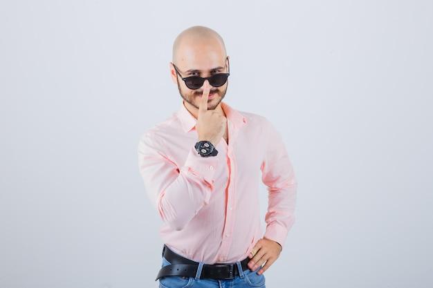 Młody człowiek dostosowując okulary w różowej koszuli, dżinsach i fajnie wyglądający. przedni widok.