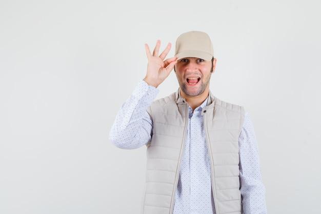 Młody człowiek dotykając czapkę w koszuli, kurtce bez rękawów, czapce i patrząc wesoło, widok z przodu.