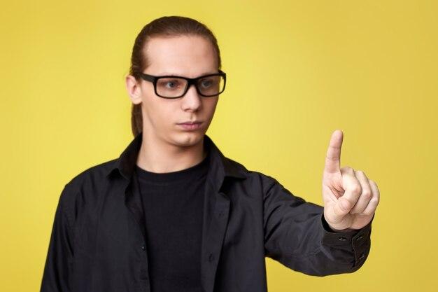 Młody człowiek dotykając wirtualnego ekranu na żółtym tle w okularach. skup się na palcu