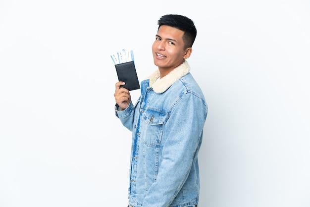 Młody człowiek ekwadoru na białym tle szczęśliwy na wakacjach z paszportem i biletami lotniczymi