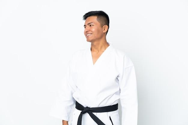 Młody człowiek ekwadoru robi karate na białym tle na białej ścianie patrząc z boku