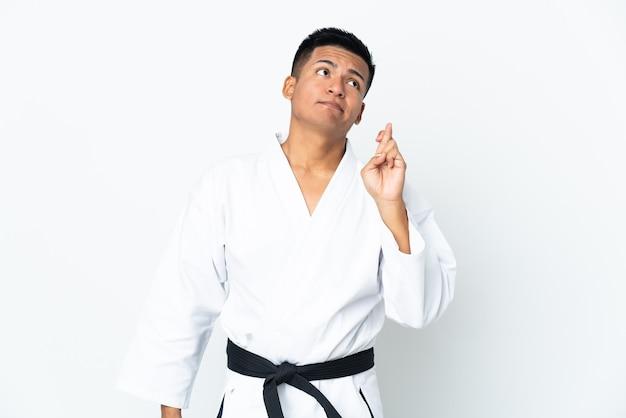 Młody człowiek ekwadoru robi karate na białym tle na białej ścianie z palcami skrzyżowanymi i pragnąc jak najlepiej