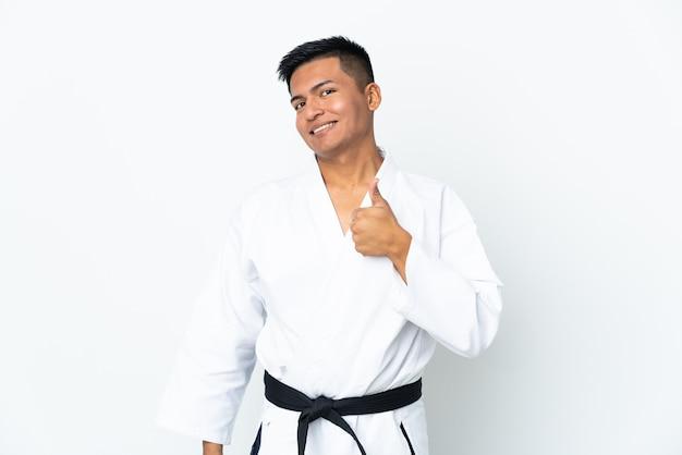 Młody człowiek ekwadoru robi karate na białym tle na białym tle, dając kciuki do góry gest