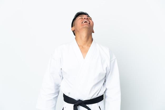 Młody człowiek ekwadoru robi karate na białym tle śmiejąc się