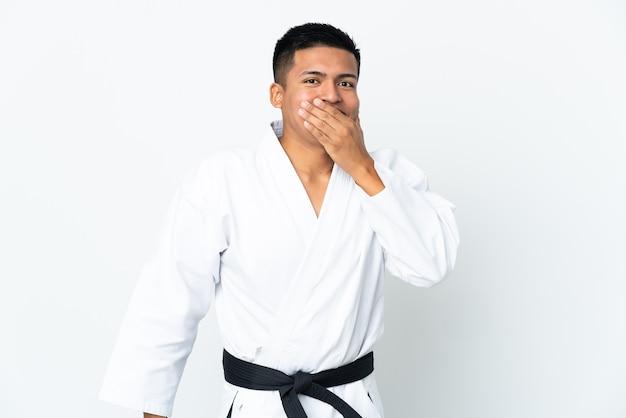Młody człowiek ekwadoru robi karate na białym tle szczęśliwy i uśmiechnięty obejmujące usta ręką