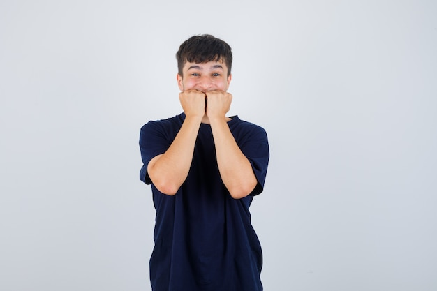 Młody człowiek emocjonalnie gryzie pięści w czarnej koszulce i wygląda na przestraszonego. przedni widok.