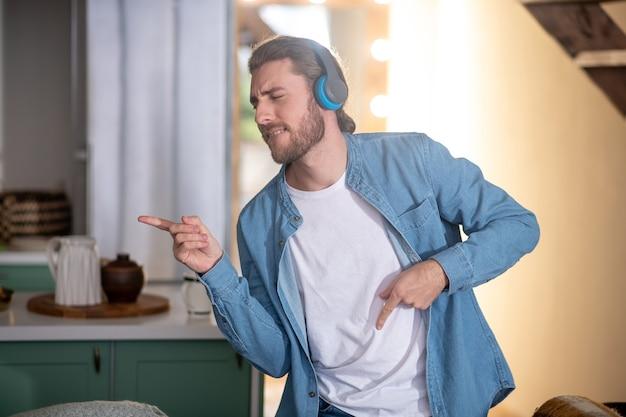 Młody człowiek emocjonalny tańczy słuchając ulubionej muzyki