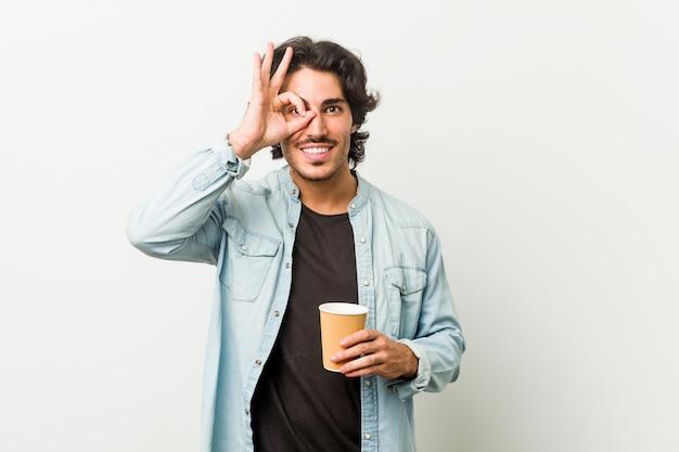 Młody człowiek fajny picia kawy podekscytowany, trzymając ok gest na oko.