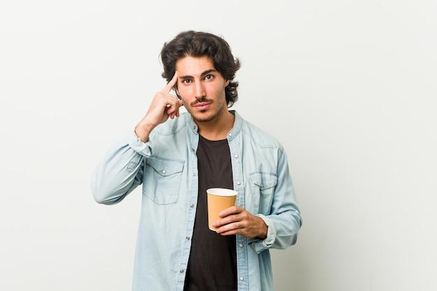Młody człowiek fajny picia palcem wskazującym kawy wskazując świątynię, myśląc, skupiony na zadaniu.
