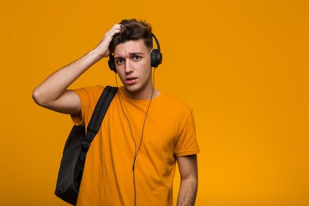 Młody człowiek fajny student słuchania muzyki w słuchawkach wesoły uśmiech wskazuje na przód.
