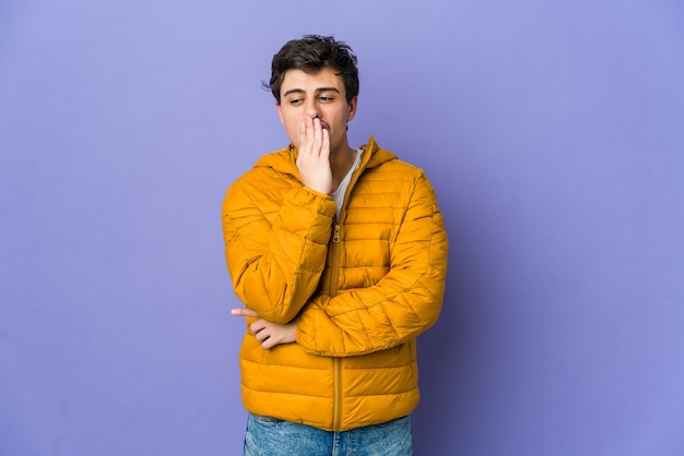 Młody człowiek fajny ziewanie pokazujący gest zmęczenia obejmujący usta ręką.