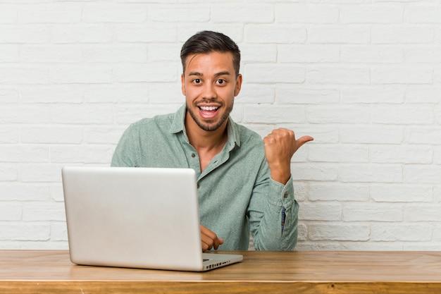 Młody człowiek filipina siedzi pracy z laptopem wskazuje palcem kciuka, śmiejąc się i beztroski.