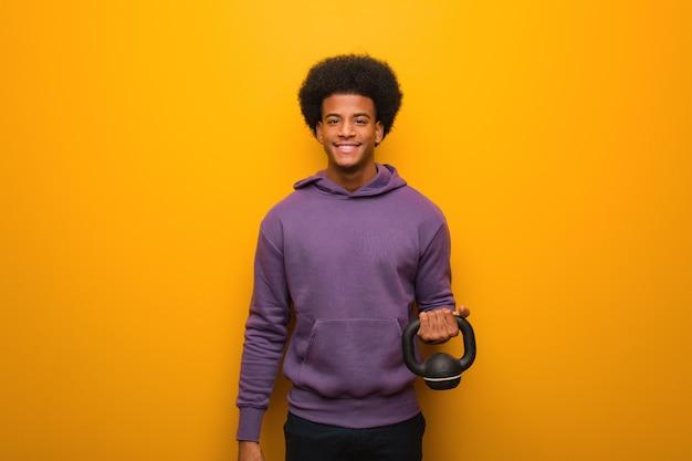 Młody człowiek fitness african american gospodarstwa hantle wesoły z uśmiechem