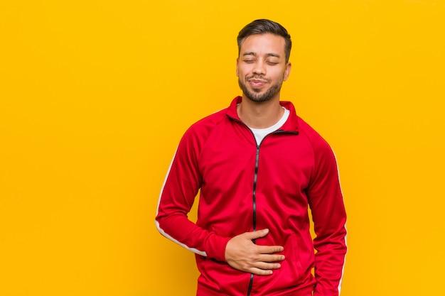 Młody człowiek fitness filipińskie dotyka brzucha, uśmiecha się delikatnie, koncepcja jedzenia i satysfakcji.