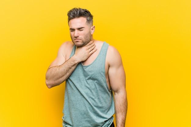 Młody człowiek fitness na żółtej ścianie cierpi na ból gardła z powodu wirusa lub infekcji.