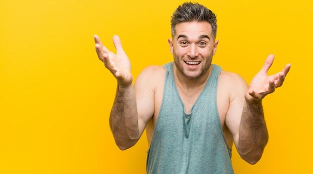 Młody człowiek fitness na żółto otrzymujący miłe zaskoczenie, podekscytowany i podnoszący ręce.
