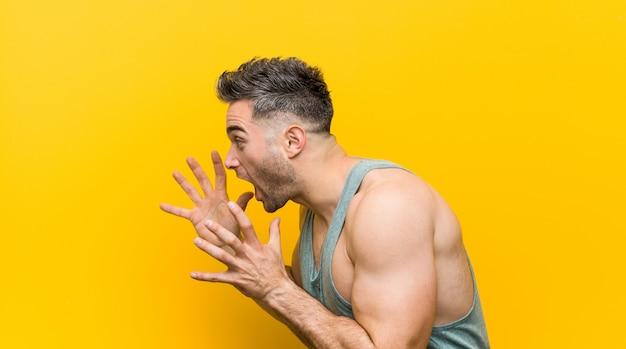 Młody człowiek fitness na żółtym tle krzyczy głośno, ma otwarte oczy i ręce napięte.