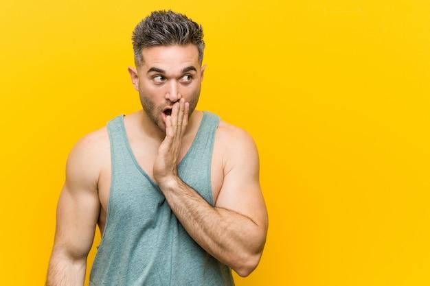 Młody człowiek fitness na żółtym tle mówi tajemniczą wiadomość o hamowaniu na gorąco i odwraca wzrok