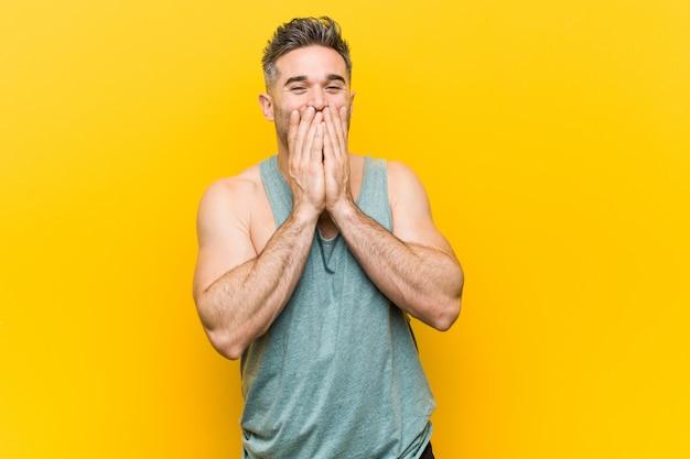 Młody człowiek fitness przeciwko żółty śmiejąc się z czegoś, obejmujące usta rękami.