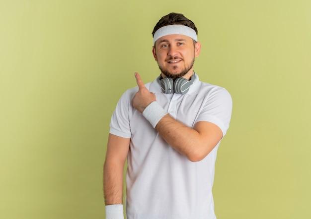 Młody człowiek fitness w białej koszuli z pałąkiem na głowę, patrząc do przodu, uśmiechnięty, wskazując palcem na bok, stojąc na ścianie oliwnej