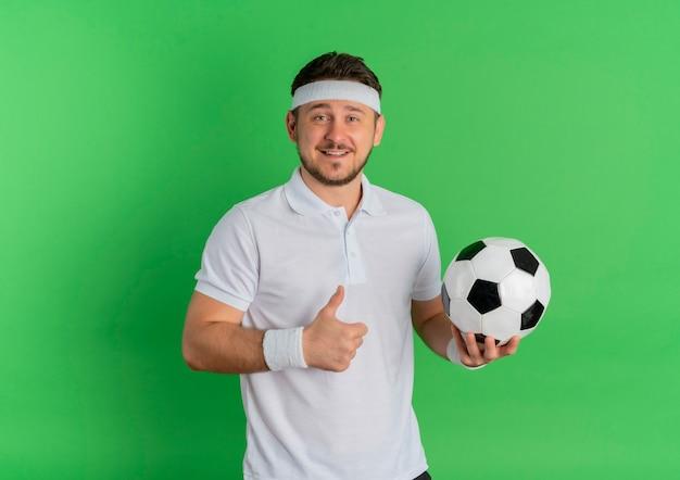 Młody człowiek fitness w białej koszuli z pałąkiem na głowę, trzymając piłkę nożną uśmiechnięty radośnie pokazując kciuki stojąc na zielonym tle
