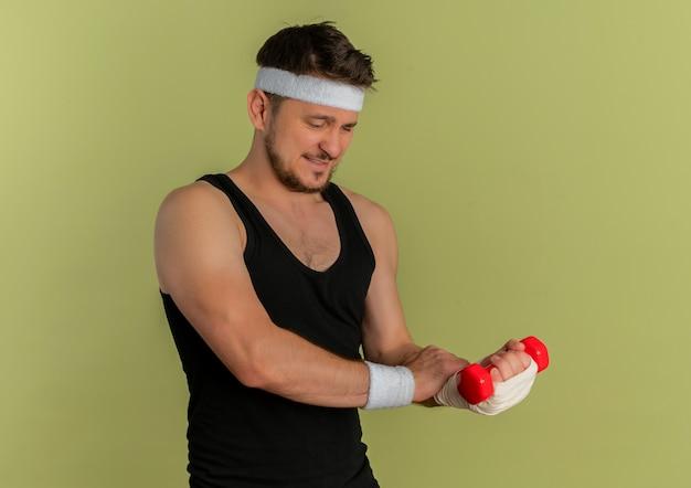 Młody człowiek fitness z pałąkiem na głowę, ćwiczenia z hantlami, patrząc na jego zabandażowany nadgarstek, czując ból stojąc na oliwkowym tle