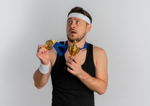 Młody człowiek fitness z pałąkiem na głowę i złotym medalem na szyi, trzymając trofeum patrząc na bok z wyrazem strachu stojącym na białym tle