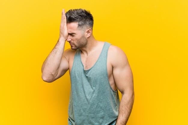 Młody człowiek fitness zapominając coś, uderzając czoło dłonią i zamykając oczy.