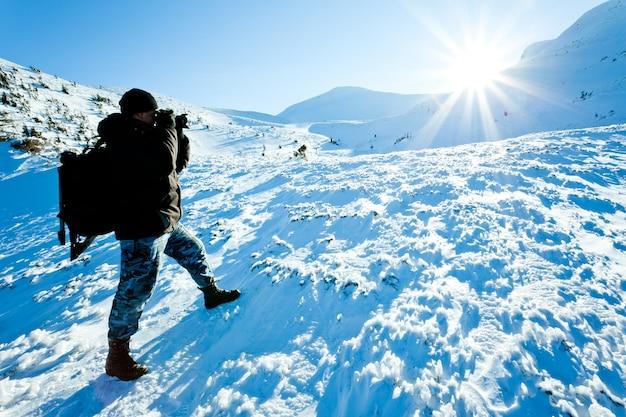 Młody człowiek fotograf w zimowej odzieży stojącej i robienie zdjęć z aparatem w słońcu na białym tle śniegu