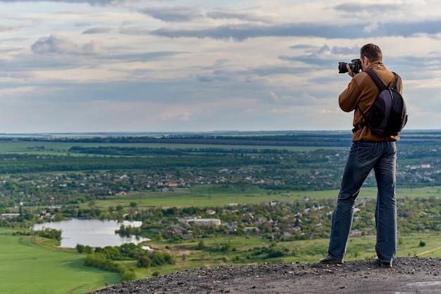 Młody człowiek fotografuje widok z lotu ptaka krajobrazu wiejskiego.