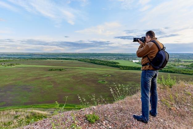 Młody człowiek fotografuje zielone pola i błękitne niebo z chmurami.