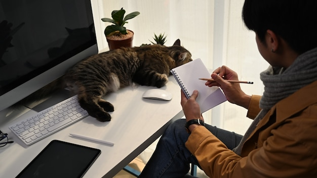 Młody człowiek freelancer robi notatkę na pusty notatnik siedząc ze swoim kotem w domu.
