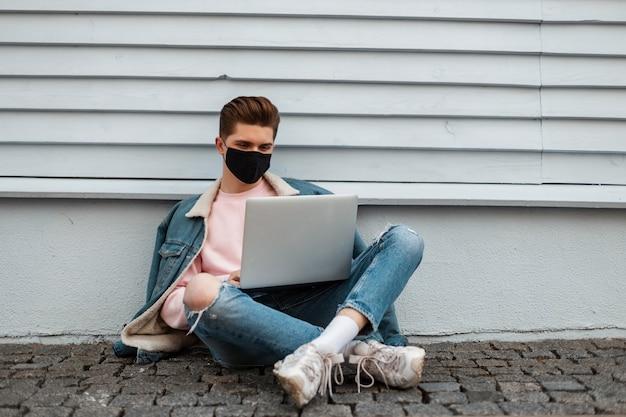 Młody człowiek freelancer w modne ubrania jeansowe z laptopem siedzi na kamiennej płytce w pobliżu domu w mieście. profesjonalny facet w dżinsach nosić w menedżerze stroju czarna maska działa na ulicy. kwarantanna. covid19.