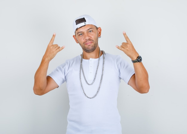 Młody człowiek gestykuluje palcami jako raper w białej koszulce, czapce, łańcuszkowym naszyjniku i wygląda pozytywnie, widok z przodu.