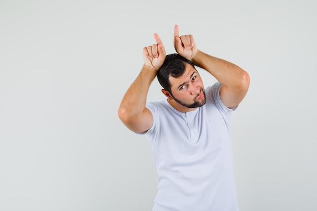 Młody człowiek gestykuluje palcami nad głową jako rogi byka w koszulce i wygląda śmiesznie. przedni widok. miejsce na tekst