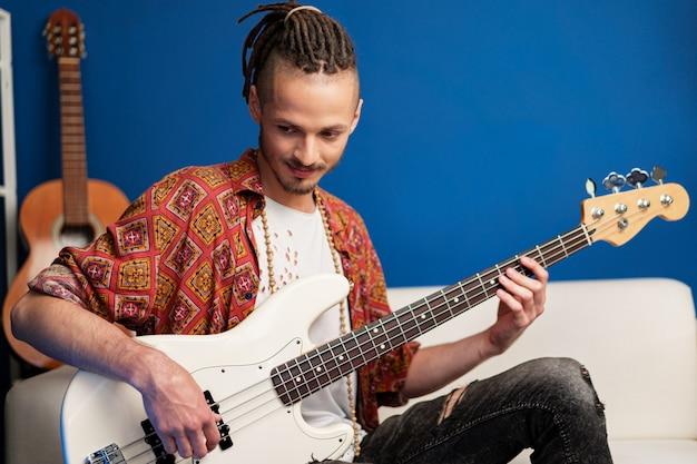 Młody człowiek gitarzysta siedzi i wykonuje