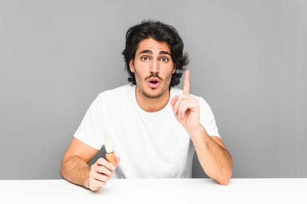 Młody człowiek goli brodę, mając świetny pomysł