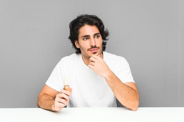 Młody człowiek goli brodę, patrząc na boki z powątpiewającym i sceptycznym wyrazem twarzy.