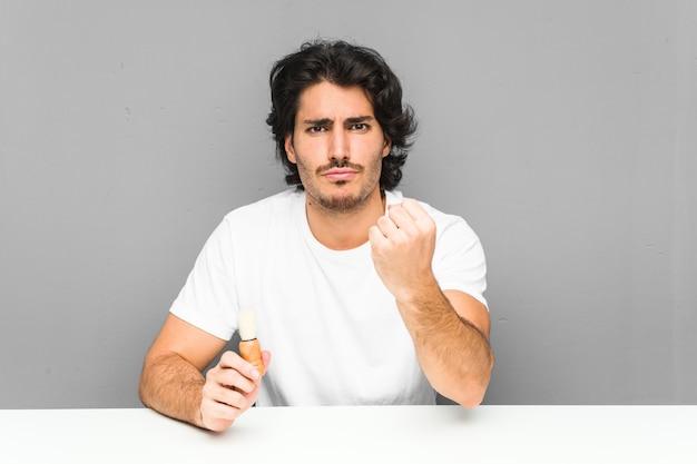 Młody człowiek goli brodę pokazując pięść, agresywny wyraz twarzy.