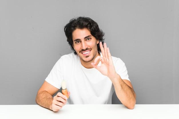 Młody człowiek goli brodę wesoły i pewny siebie, pokazując gest ok.