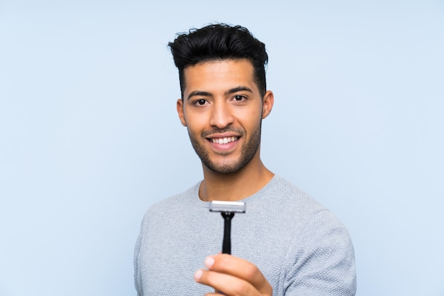 Młody człowiek goli brodę z szczęśliwym wyrażeniem