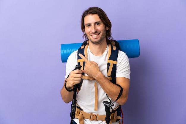 Młody człowiek góral z dużym plecakiem, wskazując w bok, aby przedstawić produkt
